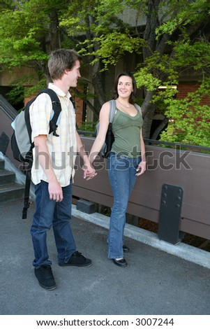 Two students holding hands while walking at school - stock photo