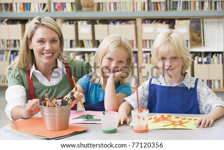 Two students in art class with teacher - stock photo