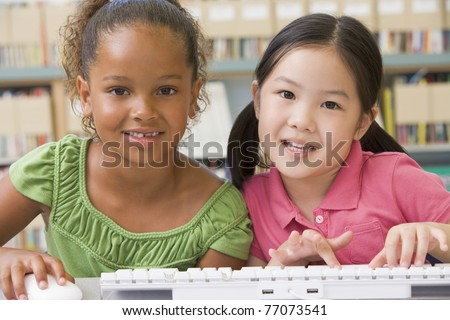 Two students in class at computer keyboard - stock photo