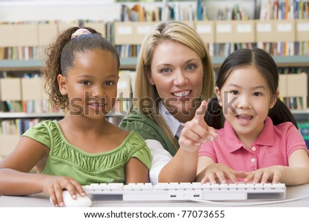 Two students in class at computer keyboard with teacher - stock photo
