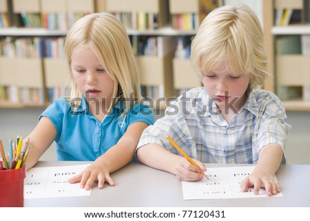 Two students in class learning letters - stock photo