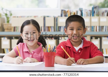 Two students in class writing