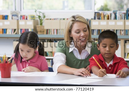 Two students in class writing with teacher helping - stock photo