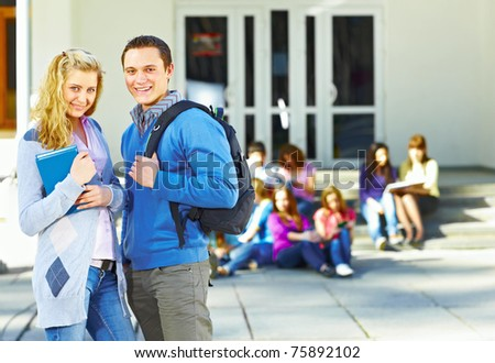 Two students in front of group of students near the university