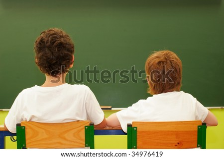 Two students in the classroom with blackboard as background - stock photo