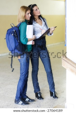 Two students in the university corridor noting down something - stock photo