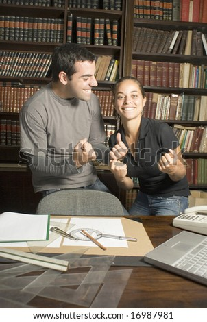 Two students joking around in library with paperwork, drafting tools, phone, and rulers on desk. Vertically framed photo. - stock photo