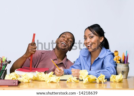 Two students laughing as they sit at a desk. Horizontally framed shot. - stock photo