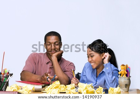 Two students laughing at each other as they sit at a desk. Horizontally framed shot. - stock photo