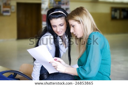 Two students learning together in the university corridor before an exam - stock photo