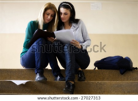 Two students learning together on the stairs - stock photo