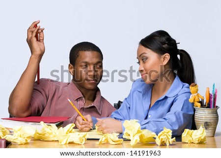 Two students looking at each other smugly as they sit at a desk. Horizontally framed shot. - stock photo