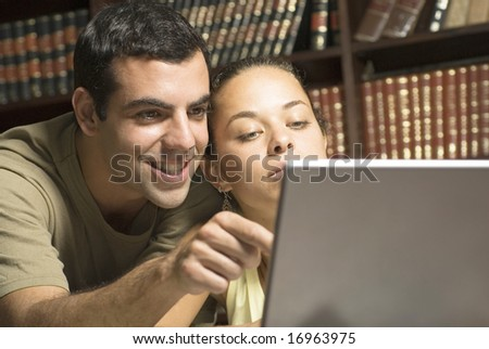 Two students looking at laptop. Horizontally framed photo. - stock photo