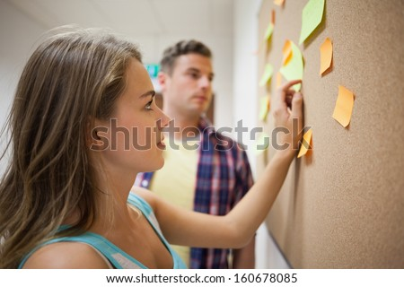 Two students looking at notice board  at college - stock photo