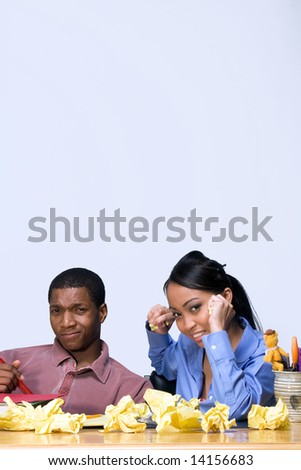 Two students looking frustrated as they sit at a desk. Vertically framed shot. - stock photo