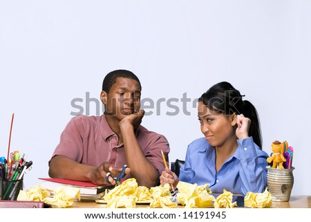 Two students looking frustrated at each other as they sit at a desk. Horizontally framed shot. - stock photo