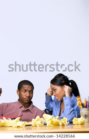 Two students looking frustrated at each other as they sit at a desk. Vertically framed shot. - stock photo