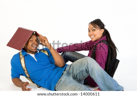 Two students seated on the floor joke around, they are both smiling and he has a notebook on his head. Horizontally framed photograph. - stock photo
