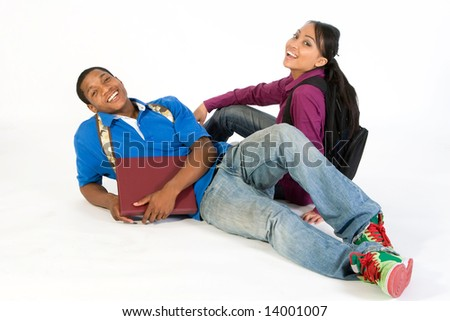 Two students seated on the floor joke around, they are smiling and laughing. They wear backpacks and he holds a notebook. Horizontally framed photograph.