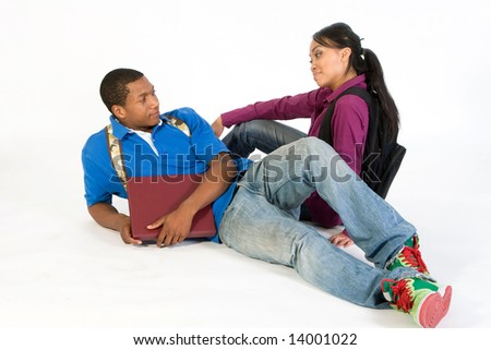 Two students seated on the ground wearing serious expressions and backpacks. He holds a notebook. Horizontally framed photograph - stock photo