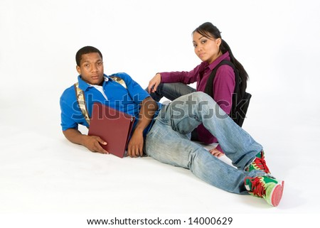 Two students seated on the ground wearing serious expressions and backpacks. Horizontally framed photograph - stock photo
