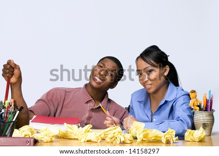 Two students sit at a desk with perplexed expressions.Horizontally framed shot. - stock photo