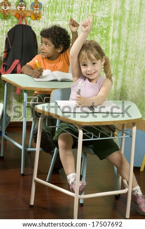 Two students sitting at desks in a classroom.  They have their hands raised.  Vertically framed shot. - stock photo