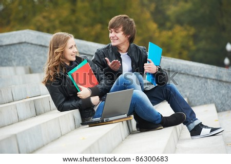 Two students sitting in park on grass with computer notebook - stock photo
