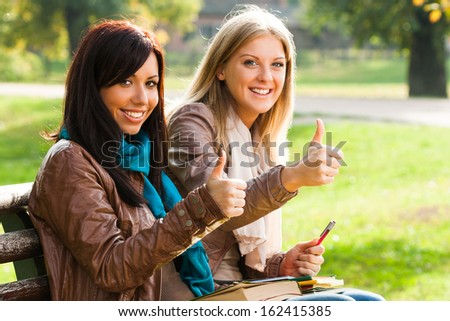 Two students sitting in the park and showing ok sign,Thumbs up for education - stock photo