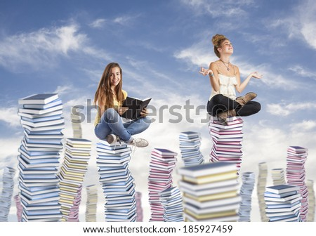 two students sitting on a high books pile - stock photo