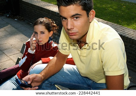 Two students sitting on school playground - stock photo