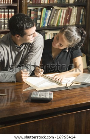 Two students smiling at each other as they work at a desk with a laptop, calculator, ruler, and calculator on it. Vertically framed photo. - stock photo