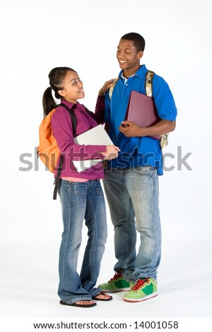 Two students stand and look at  each other with happy expressions on their faces. They wear backpacks and he carries a notebook. She has her arm n his shoulder. Vertically framed photograph. - stock photo