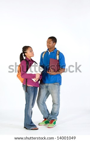 Two students stand and look at  each other with worried expressions on their faces. They wear backpacks and he carries a notebook. Vertically framed photograph. - stock photo