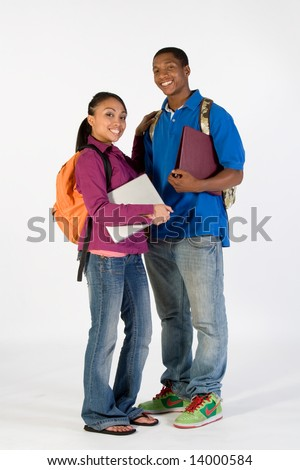 Two students stand and look at  the camera while smiling. They wear backpacks and he carries a notebook. Vertically framed photograph. - stock photo