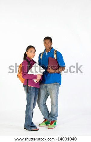 Two students stand and look at  the camera with serious expressions on their faces. They wear backpacks and he carries a notebook. Vertically framed photograph. - stock photo
