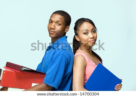 Two students standing back to back carrying books. Horizontally framed photograph - stock photo