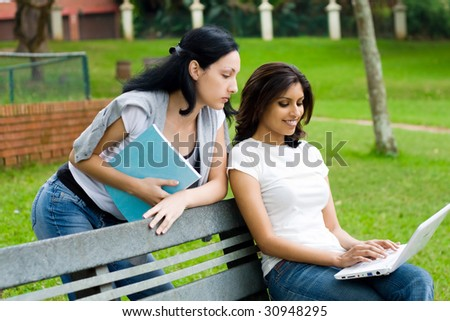 two students studying computer outdoors - stock photo