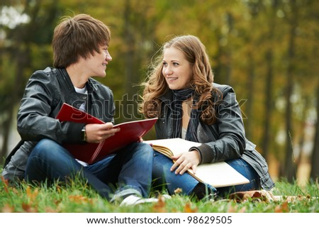 Two students studying in park on grass with notebook outdoors - stock photo