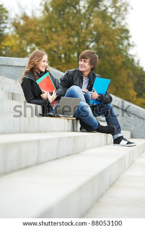 Two students studying with computer notebook and workbooks outdoors - stock photo