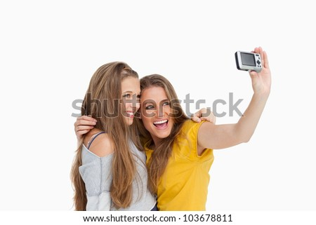 Two students taking a picture of themselves against white background - stock photo