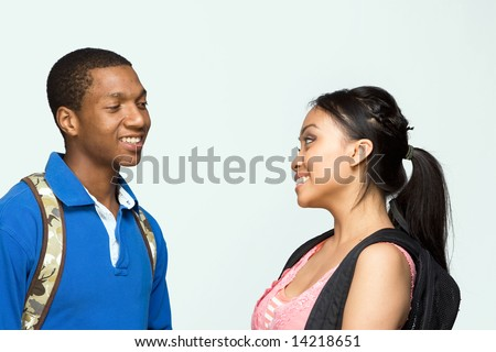 Two students wearing backpacks look at each other and laugh. Horizontally framed photograph - stock photo