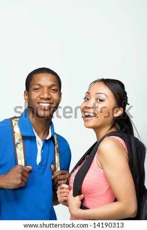 Two students wearing backpacks look at the camera and smile. Vertically framed photograph