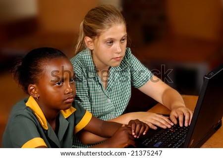 Two students working on a laptop with selective focus - stock photo