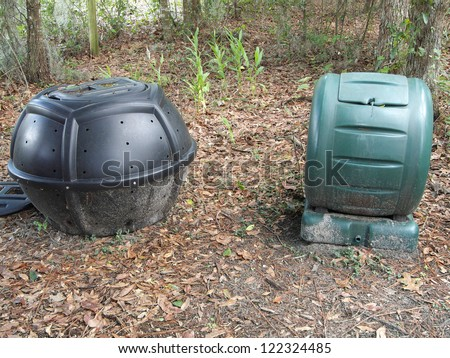 Two styles of compost bins: a rolling composter and a compost tumbler. - stock photo