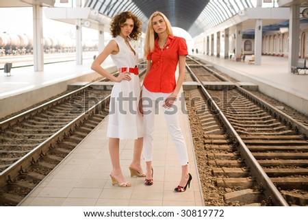 Two stylish girls on railway station - stock photo