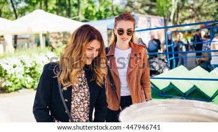 Two stylish ladies in sunglasses are enjoying their walk in a park. One girl with brown unbounded hair is wearing black jacket. Another girl is wearing brown jacket. - stock photo