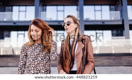 Two stylish ladies in sunglasses are enjoying their walk on the street. . One girl with unbounded brown hair is wearing motley dress. Another girl is wearing brown leather jacked above white blouse - stock photo