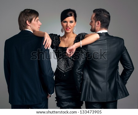 Two stylish men in suits and a girl in an evening black dress - stock photo