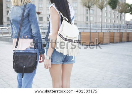 Two stylish women legs in blue jeans and shorts holding messenger leather bag and backpack in hand. Street fashion outfit